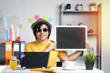 Young Man Holding Empty Blackboard   While Working on Summer Vacation Season at Office