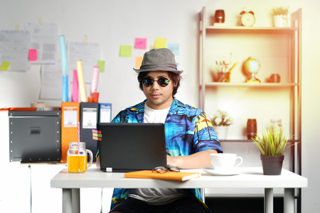 Hawaiian Young Man Working With Laptop on Summer Vacation Season at Office