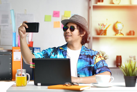 Stylish Young Man Taking Picture While Working on Summer Vacation Season at Office