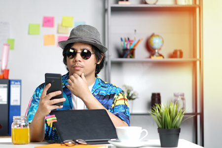 Stylish Young Professional Checking Smartphone While Working on Summer Vacation at Office