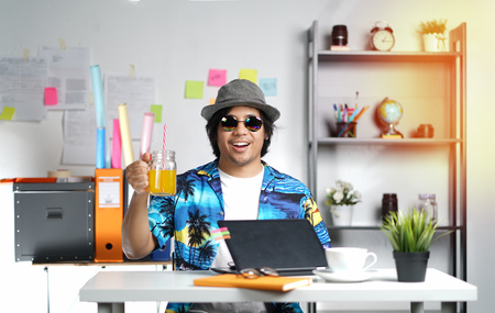 Stylish Young Man Holding Orange Juice While Working on Summer Vacation Season at Office