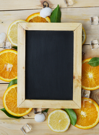 Portrait Black Board Orange Leaves Cube Ice Sea Shells Citrus Pattern on Wooden Background Copy Space Stock Photo
