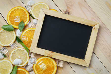 Black Board Orange Leaves Cube Ice Sea Shells Citrus Pattern on Wooden Background Copy Space