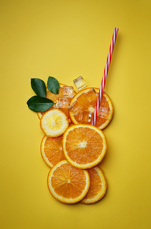 Orange Juice Concept.  Glass Of Orange  Juice Made by Sliced Citrus on Yellow Background
