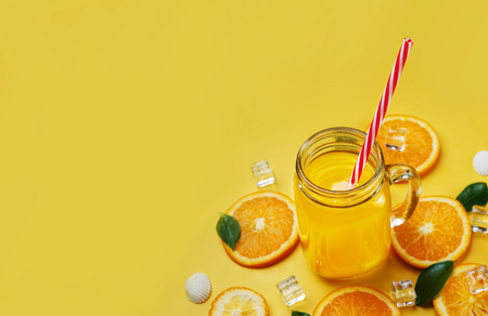 Glass of Orange Juice Leaves Citrus Ice Sea Shells Citrus on Yellow Background Copy Space Stock Photo