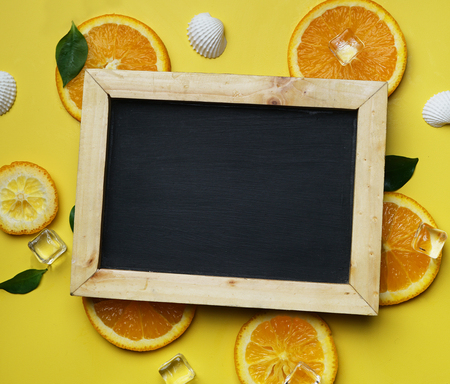 Black Board Orange Leaves Cube Ice Sea Shells Citrus Pattern on Yellow Background Copy Space
