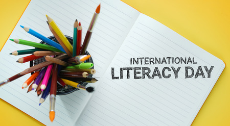 International Literacy Day. School Stationary in Basket on Opened Book Top View Yellow Background