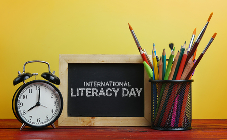 International Literacy Day. Alarm Clock, Blackboard and School Stationary in Basket on Wooden Table Yellow Background