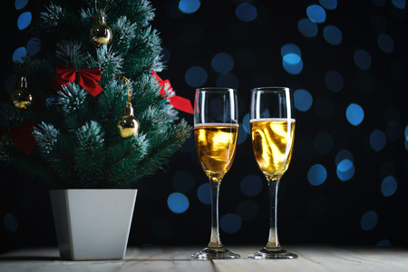 Two Glasses of Champagne and Small Christmas Tree Dark Glow Lights Background.