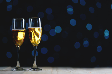 Two Glasses of Champagne Dark Glow Lights Background. Copy Space