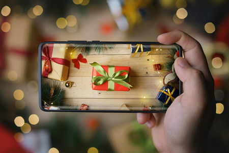 Hand Taking Picture of Christmas Present With Infinite Display Smartphone