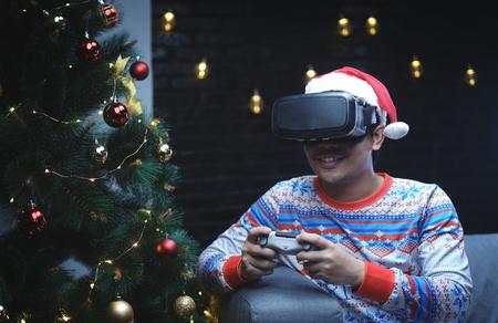 Asian Man With Christmas Costume Playing Virtual Reality Sitting Beside Christmas Tree