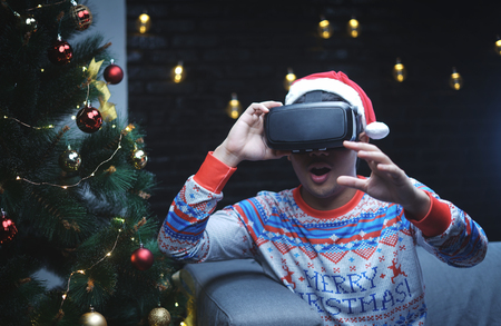 Asian Man With Christmas Costume Playing Virtual Reality Sitting Beside Christmas Tree