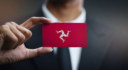 Business man Holding Card of Isle of Man Flag