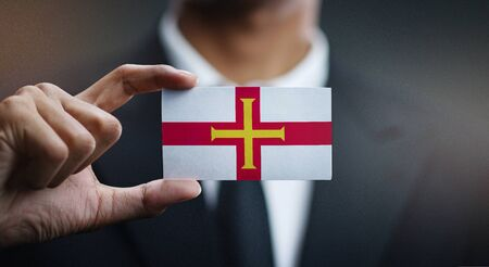 Business man Holding Card of Guernsey Flag
