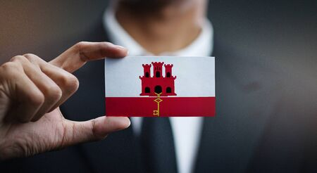 Business man Holding Card of Gibraltar Flag 스톡 콘텐츠