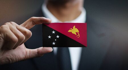 Business man Holding Card Papua New Guinea Flag