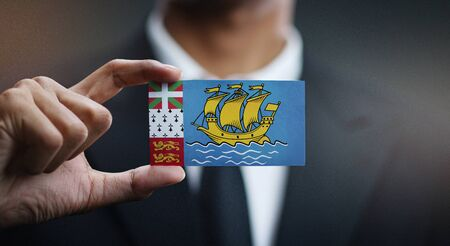 Business man Holding Card of Saint Pierre and Miquelon Flag 写真素材