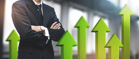 Positive Growing Business Success Concept. Asian Businessman on Blurred Office Background. 3D Green Arrow Up
