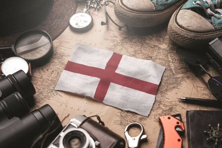 England Flag Between Traveler's Accessories on Old Vintage Map. Tourist Destination Concept.