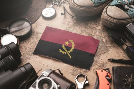 Angola Flag Between Traveler's Accessories on Old Vintage Map. Tourist Destination Concept. Tourist Destination Concept.