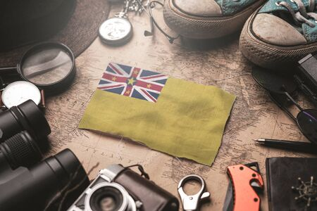 Niue Flag Between Traveler's Accessories on Old Vintage Map. Tourist Destination Concept.