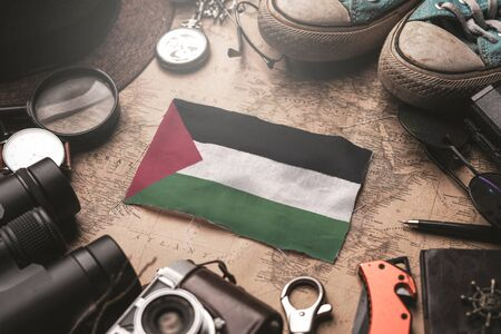 Palestine Flag Between Traveler's Accessories on Old Vintage Map. Tourist Destination Concept.                    Фото со стока
