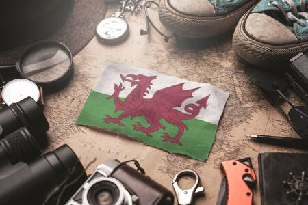 Wales Flag Between Traveler's Accessories on Old Vintage Map. Tourist Destination Concept. Foto de archivo