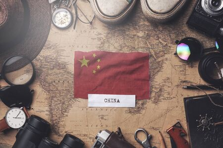 China Flag Between Traveler's Accessories on Old Vintage Map. Overhead Shot