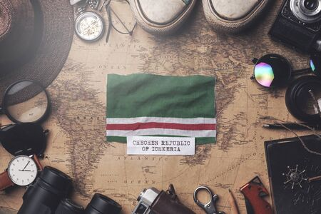 Chechen Republic of Ichkeria Flag Between Traveler's Accessories on Old Vintage Map. Overhead Shot Foto de archivo
