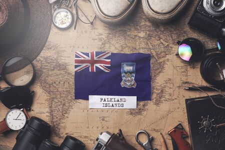 Falkland Islands Flag Between Traveler's Accessories on Old Vintage Map. Overhead Shot