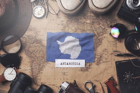 Antarctica Flag Between Traveler's Accessories on Old Vintage Map. Overhead Shot Foto de archivo