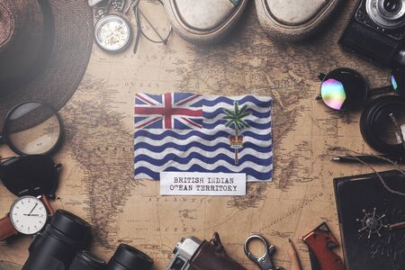 British Indian Ocean Territory Flag Between Traveler's Accessories on Old Vintage Map. Overhead Shot Foto de archivo