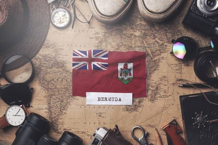 Bermuda Flag Between Traveler's Accessories on Old Vintage Map. Overhead Shot Foto de archivo