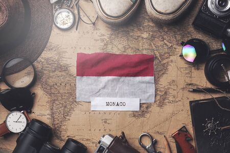 Monaco Flag Between Traveler's Accessories on Old Vintage Map. Overhead Shot
