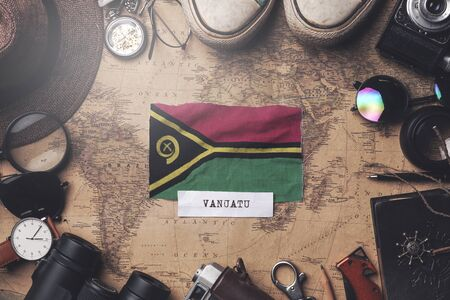 Vanuatu Flag Between Traveler's Accessories on Old Vintage Map. Overhead Shot