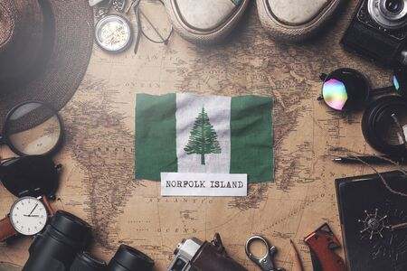 Norfolk Island Flag Between Traveler's Accessories on Old Vintage Map. Overhead Shot