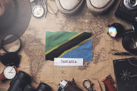 Tanzania Flag Between Traveler's Accessories on Old Vintage Map. Overhead Shot Standard-Bild