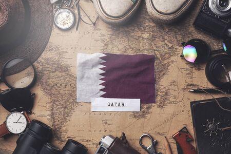 Qatar Flag Between Traveler's Accessories on Old Vintage Map. Overhead Shot Standard-Bild