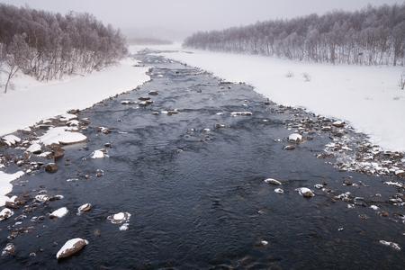 the river: fog over a frozen river in sweden