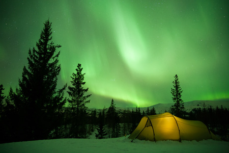 geomagnetic: illuminated tent in front of strong aurora display