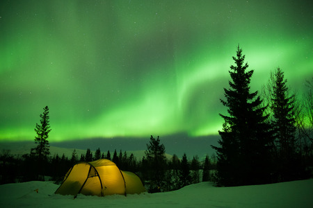 magnetosphere: illuminated tent in front of strong aurora display