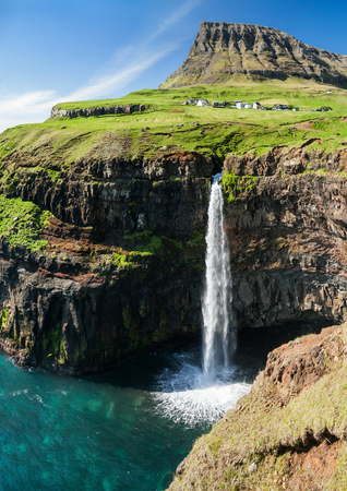 sea cliff: waterfall on faroe islands and the village Gasadalur in background Stock Photo