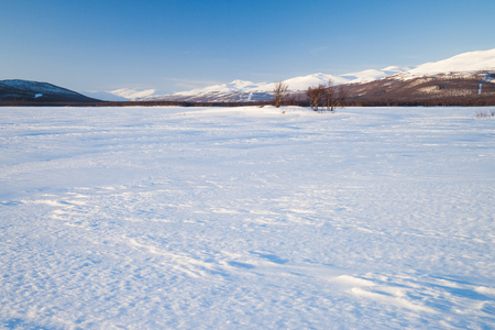 snowy field: evening mood over a frozen lake in sweden Stock Photo