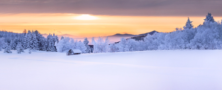 Panorama of an idyllic white winter landscape with a little wooden hut in background