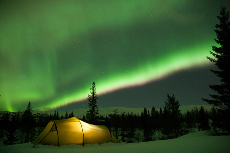 illuminated tent in front of strong aurora display