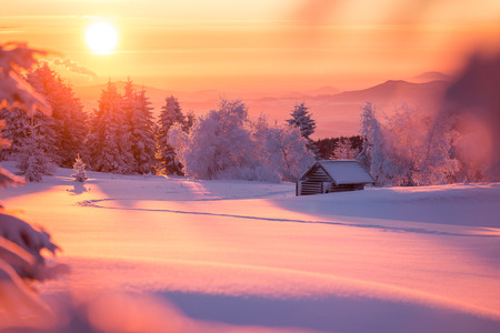 Golden sunlight over a idyllic white winter landscape with a little wooden hut in background