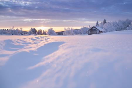 erzgebirge: Golden sunlight over an idyllic white winter landscape with a little wooden hut in background