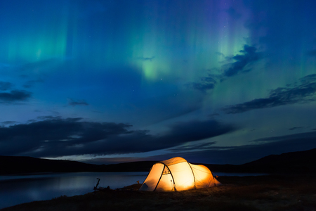 iluminated: Northern lights dancing over an iluminated tent in Norway