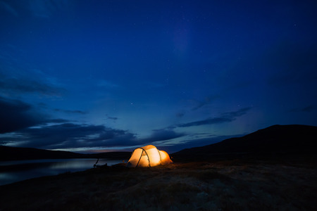 Northern lights dancing over an iluminated tent in Norway